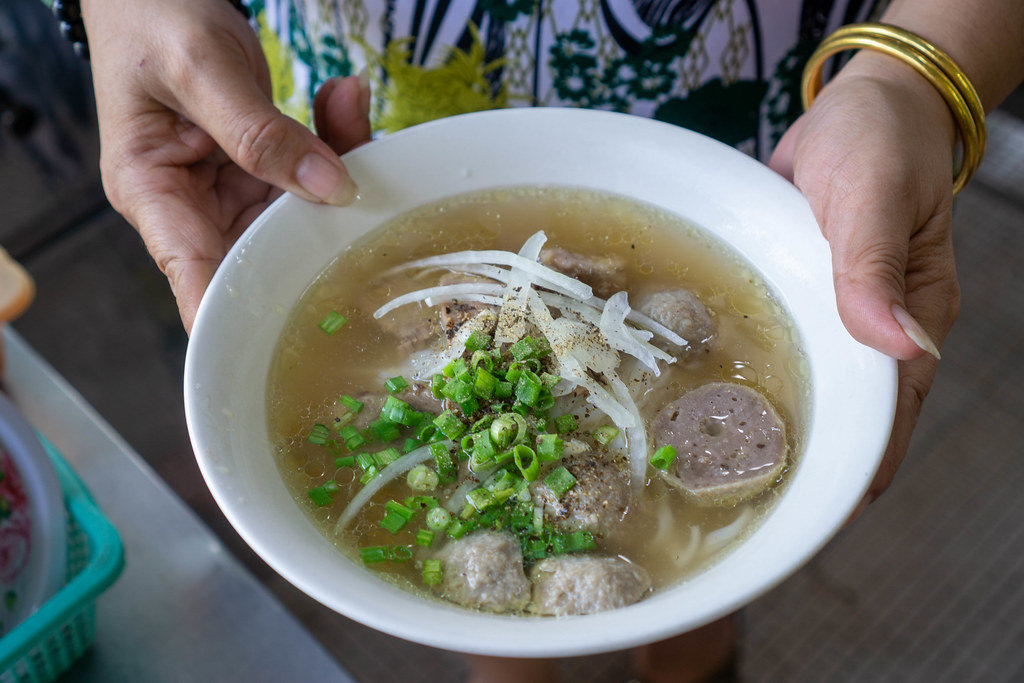 Close Up Photo of Vietnamese Street Food Seller holding a Bowl of Fresh Pho Bo with Beef Balls, Onions and Spring Onions