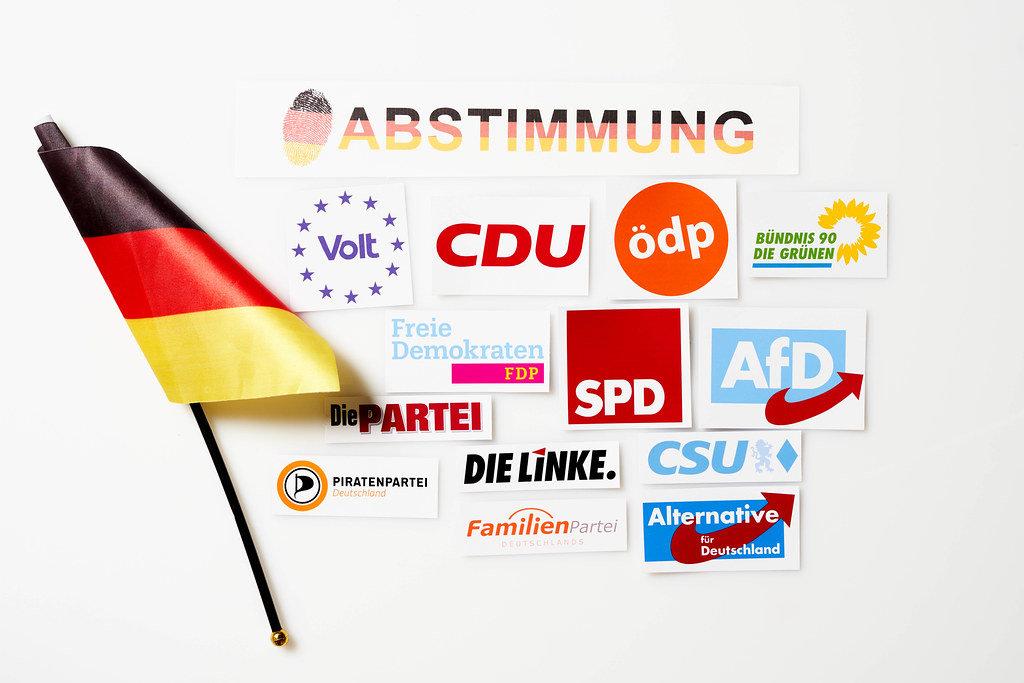 Deutsche Politik 2021 - Abstimmung in der Bundestagswahl. Parteilogos und deutsche Flagge
