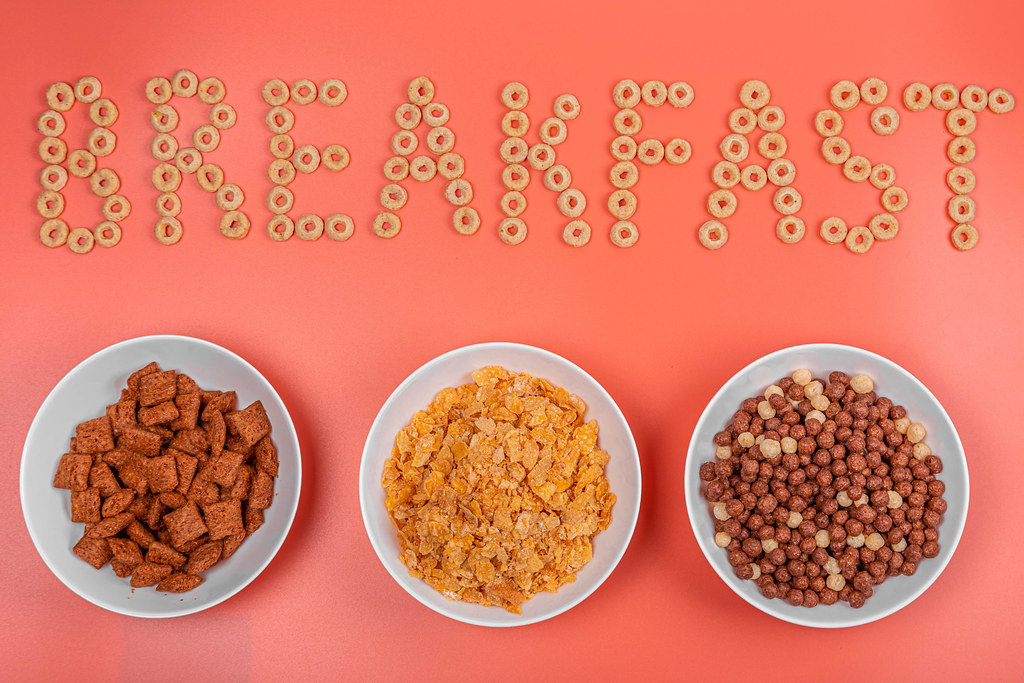 Breakfast background with three bowls of ready-made breakfast corn on pink backdrop, top view