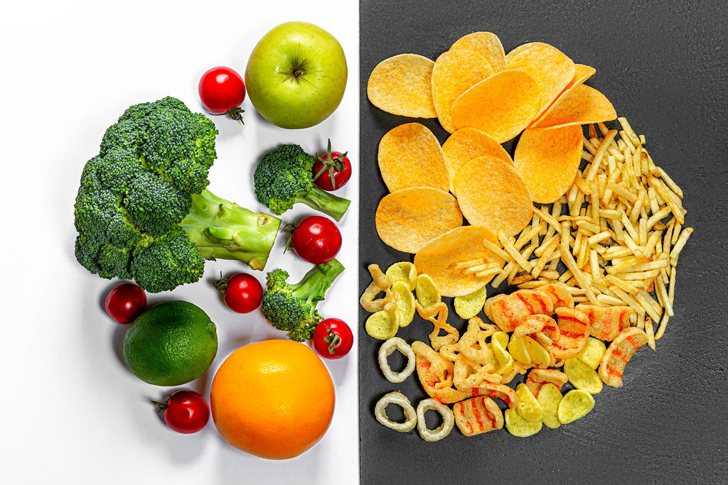 Lifestyle choice concept. Healthy food on white and junk food on a black background. Top view