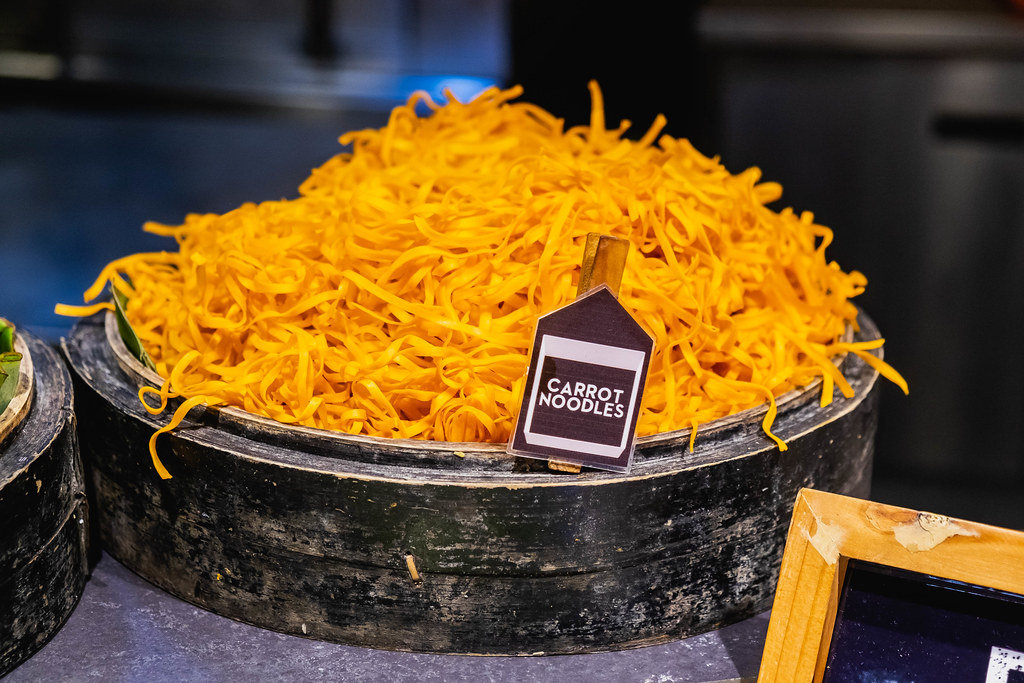 Carrot noodles on wooden bowl