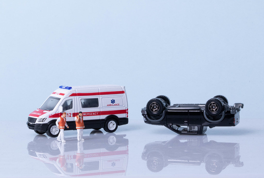 Car crash concept with ambulance and medical workers