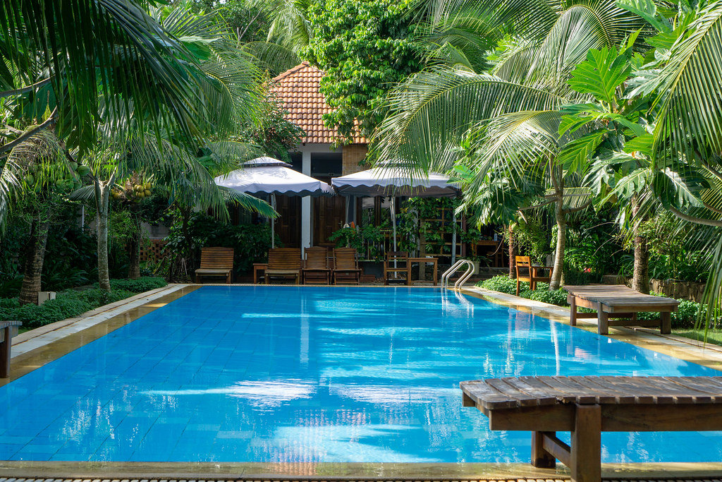 Swimming Pool with Sunbeds and Garden at a Hotel with many Villas and Palm Trees on Phu Quoc Island, Vietnam