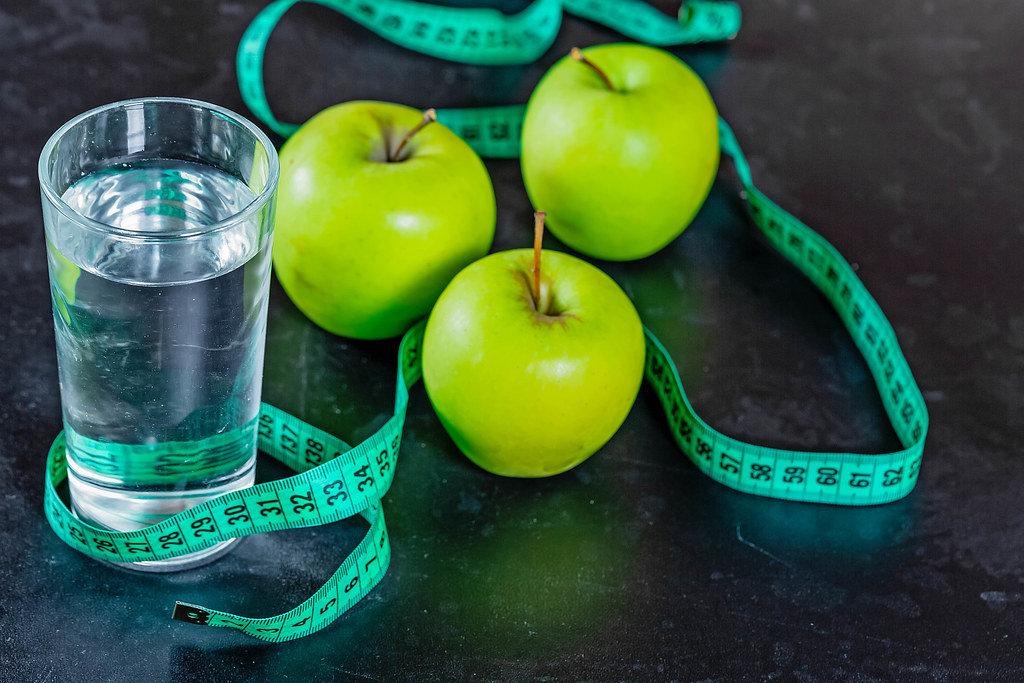 Abnehmen - Grüne Äpfel mit einem Glas Wasser und einem Maßband auf schwarzem Hintergund