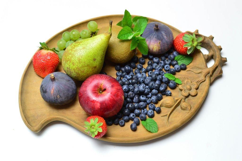 Birne mit Apfel, Kiwi, Feigen, Erdbeeren, Blaubeeren und Weintrauben auf Obstschale