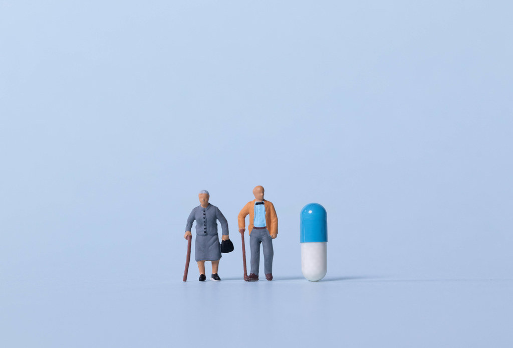 Older couple with pill on light blue background