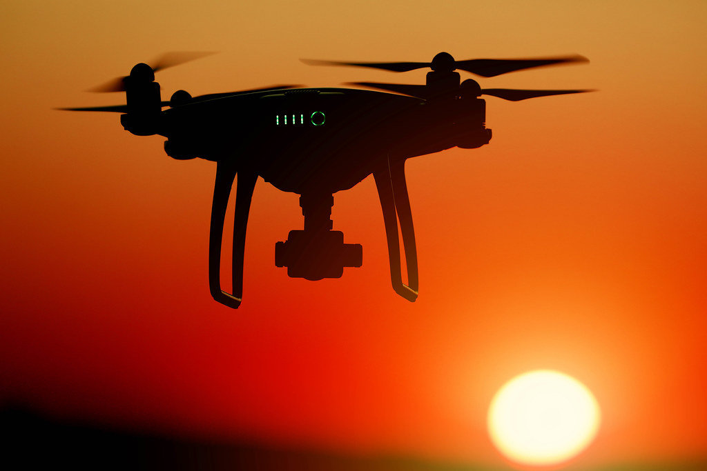 Silhouette of drone at sunset, orange sky
