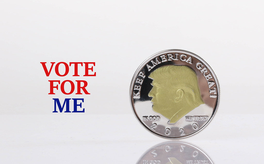 Silver coin with Donald Trump on it and Vote for me text