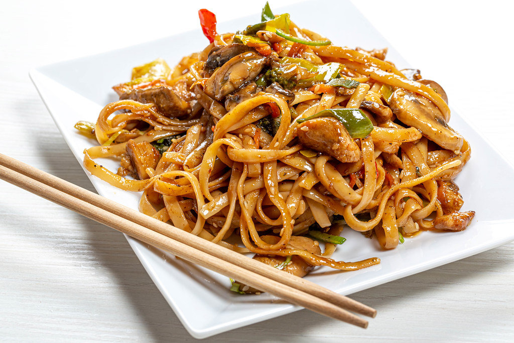 Rice noodles with chicken, mushrooms and vegetables close-up