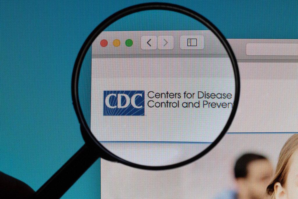 CDC Logo und Schriftzug der der US-Gesundheitsbehöre, vergrößert dargestellt unter einer Lupe