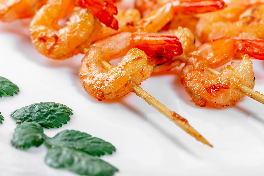 Delicious fried shrimp on wooden skewers