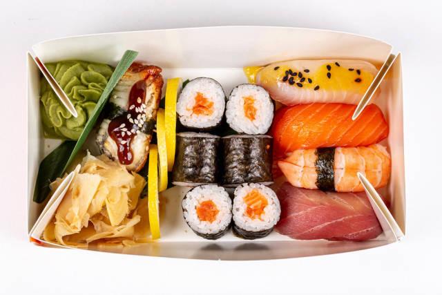 Maki rolls and nigiri in a cardboard box, top view
