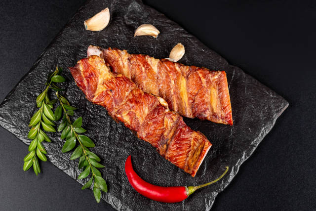Smoked ribs with red pepper chili and garlic on black, top view