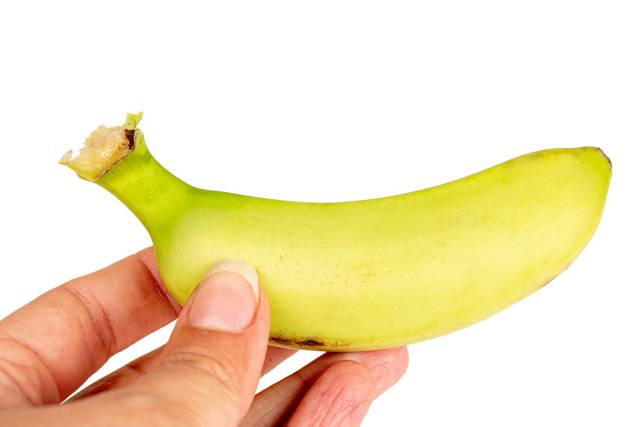 Small fresh banana in a female hand