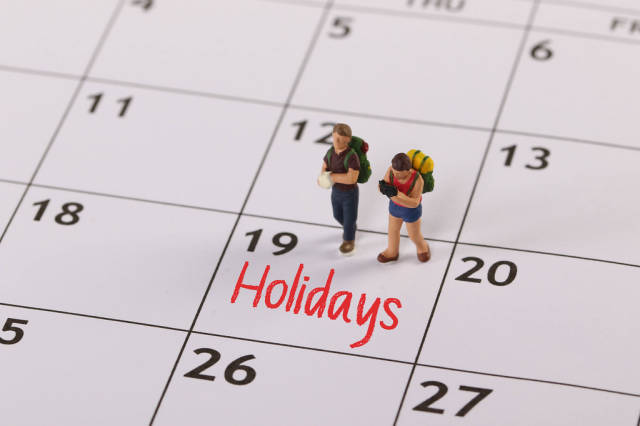 Small traveler figures with backpack standing on calendar with Holidays text