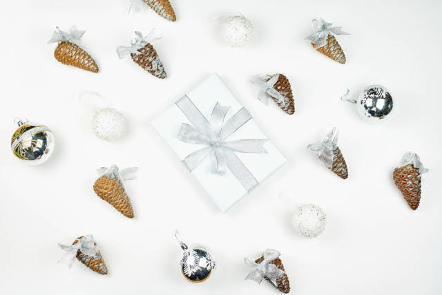 A beautiful arrangement of decorative pine cones and white X-mas giftbox