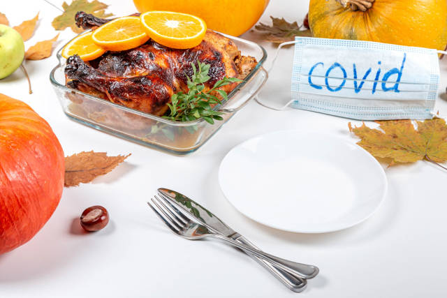 Served table on the day of Thanksgiving and medical mask with the inscription covid
