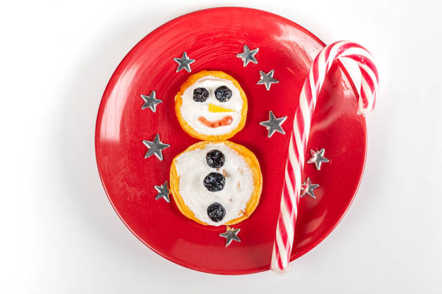 Pancakes snowman on a red plate with stars, top view