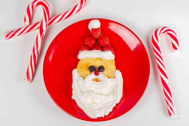 Christmas breakfast pancake santa claus with lollipop sticks, top view
