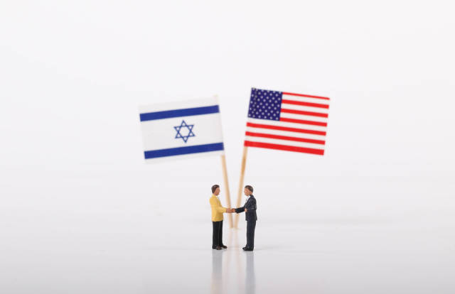 Two businessman shaking hands in front of flags of Israel and USA