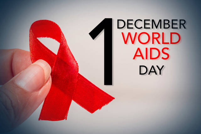 Aids red ribbon on womans hand support for World aids day