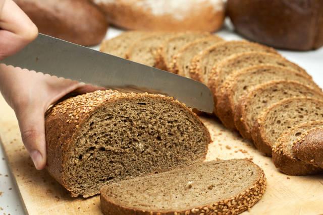 Woman hand slicing bread on cutting board