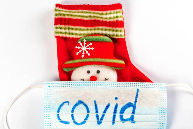 Close-up, mask with the inscription covid and christmas sock with snowman