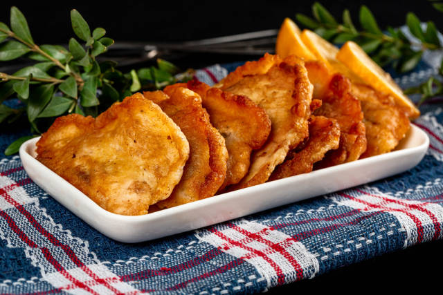 Fried fish slices in batter on a blue kitchen towel