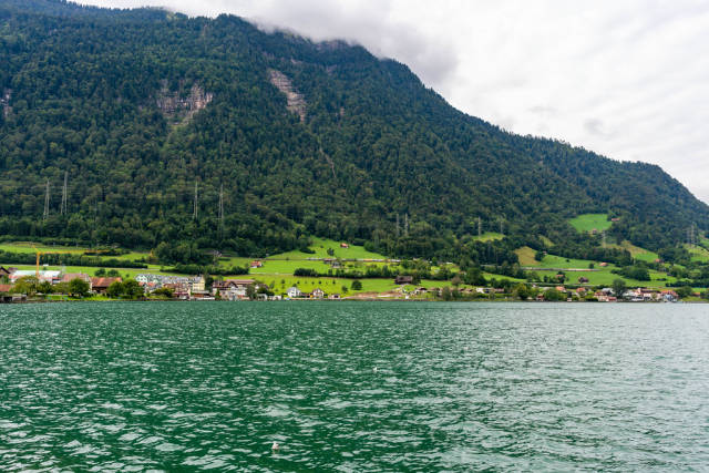 View of a Swiss village on the shore of the lake with hills disappearing into the clouds in the background