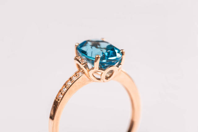 Close-up, golden ring with blue topaz on white