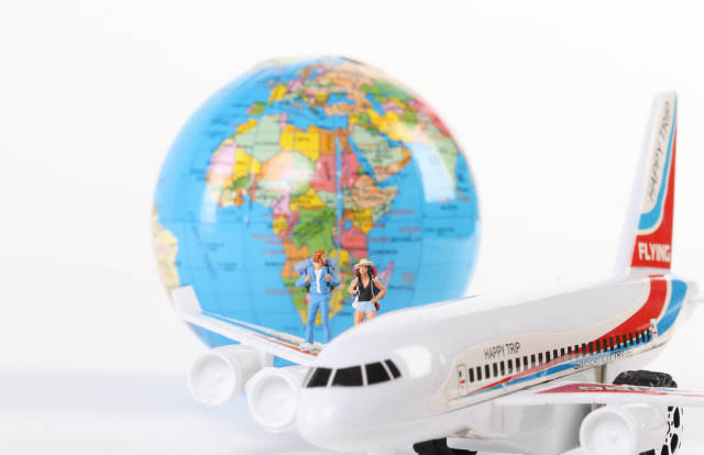 Miniature travelers with globe and airplane on white background