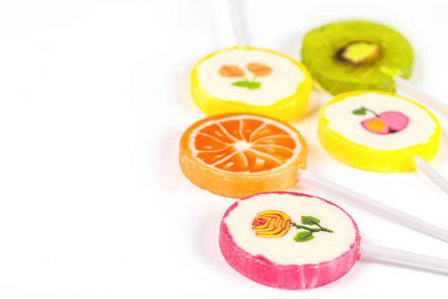 Assorted colors lollipops on white background, close-up