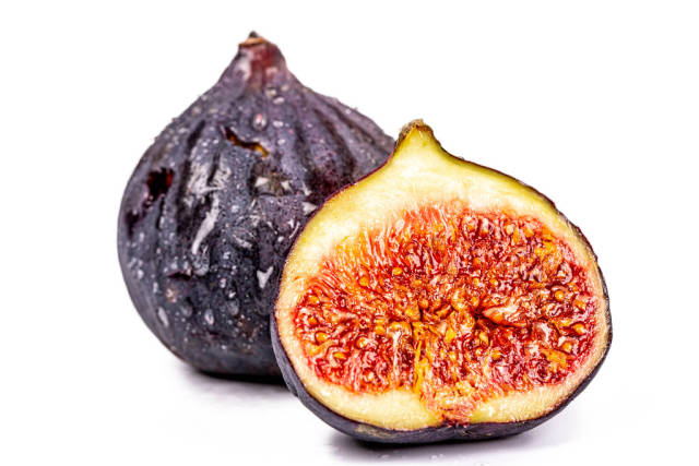 Whole and half fresh figs on white background