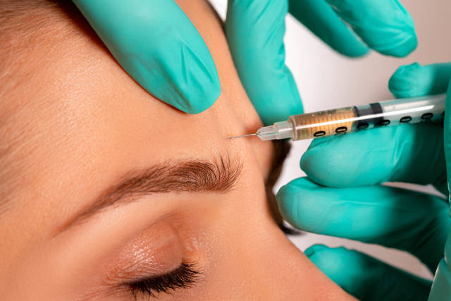 Close-up injection to smooth out wrinkles on a womans forehead