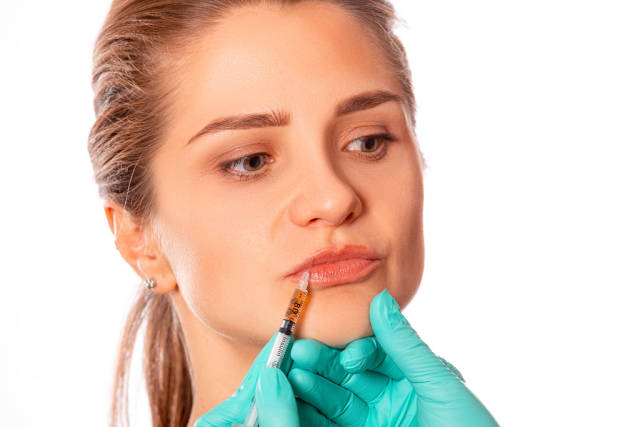 Young woman gets injection in her lips