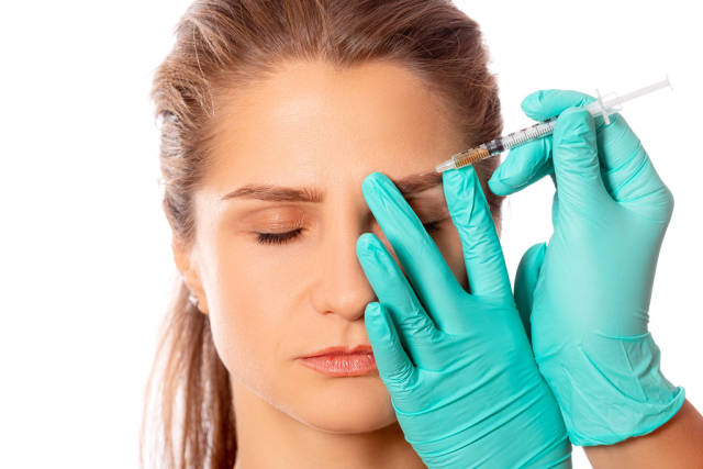 Doctors hands in gloves make an injection into the eyebrow of a girl