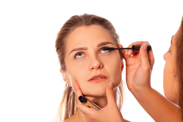 Applying mascara to a womans eyelashes