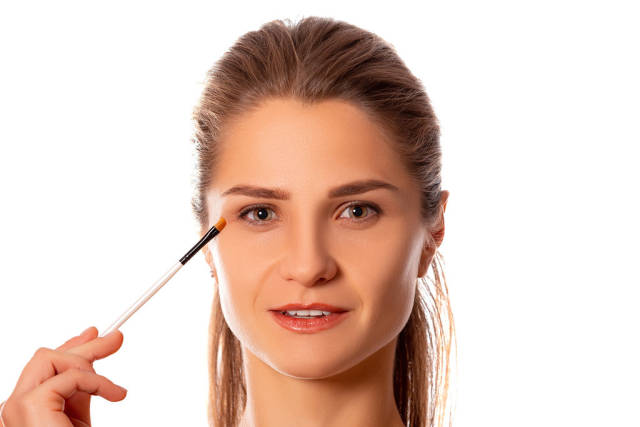Portrait of a woman with makeup brush near her eyes