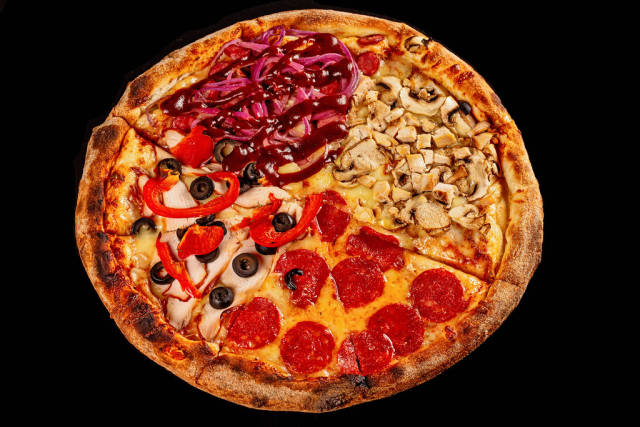 Delicious pizza with different cheeses, sausages, ham, chicken, vegetables and mushrooms