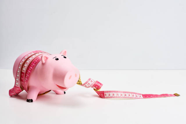 Pink piggy bank tied with tape - a symbol of the crisis