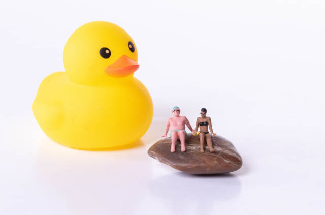 Rubber duck and couple in bathing suit sitting on rock