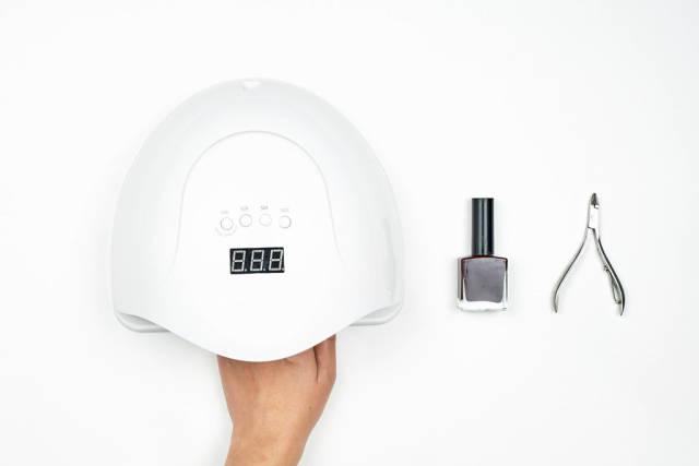 Manicured nails in uv lamp in beauty salon