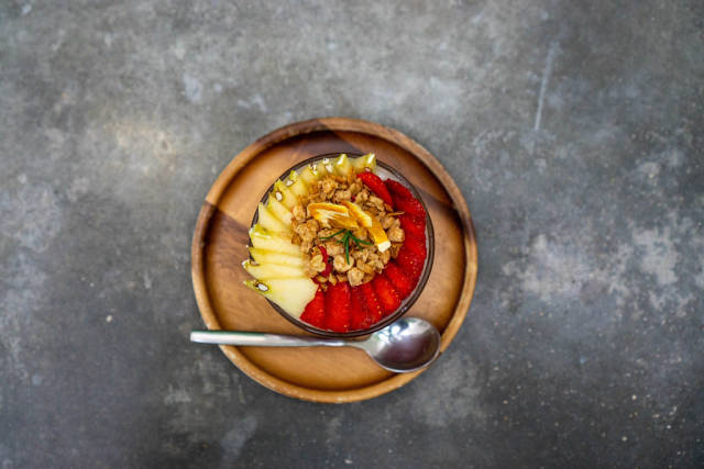 Top View Photo of Sliced Apples and Strawberries in a Glass of Yogurt with Cereals on a Wooden Plate