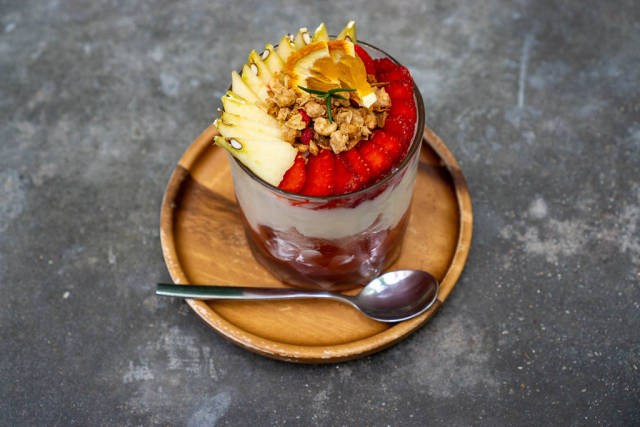 Close Up Photo of Glass with Yogurt, Cereals, Strawberries and Apples  on a Wooden Saucer with Spoon