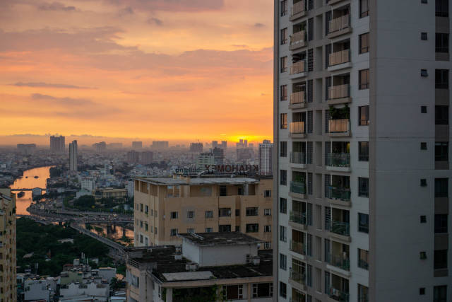 Sunset City View from an Apartment at Golden Hour with Sky Reflecting in River in Ho Chi Minh City, Vietnam