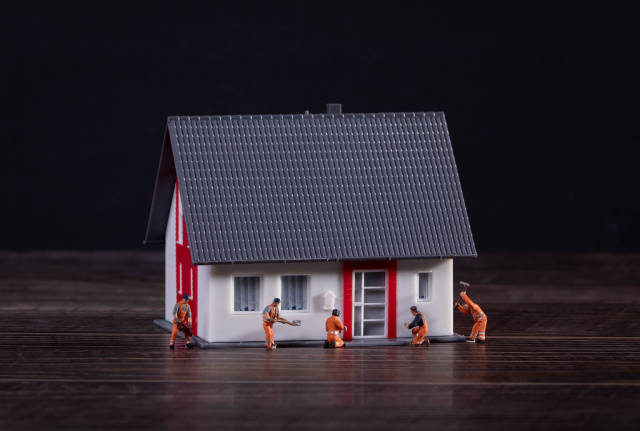 Miniature workers building a house