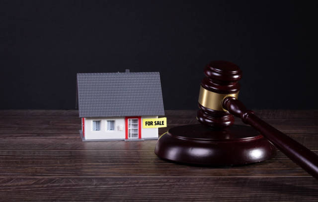 House with For sale text and wooden judge gavel