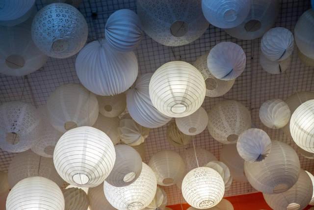 Verschiedene Deckenlampen mit und ohne Licht aus Papier als Dekoration in einem Cafe