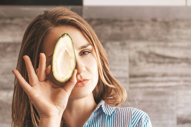 The girl with half a fresh avocado in front of her face