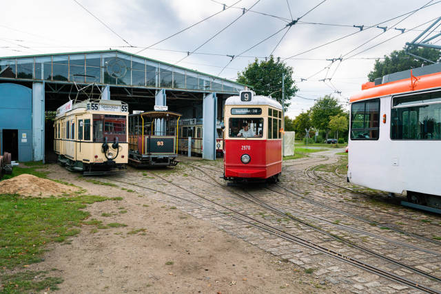 5 German retro trains of different years on the rails in front of the tram depot